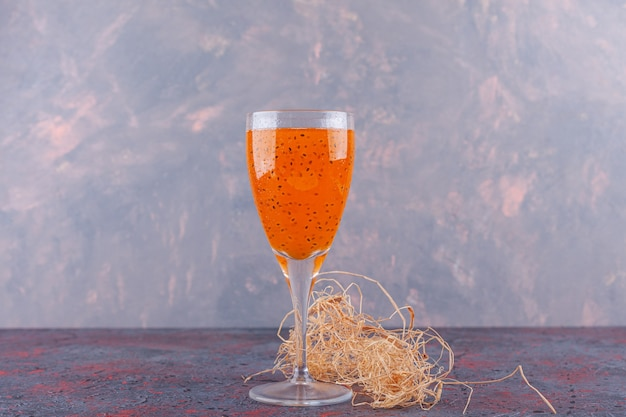 Szklanka wody mineralnej z suszonym kwiatem umieszczonym na ciemnym tle.