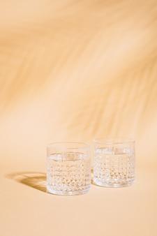 Szklanka wody na pastelowym tle z cieniem tropikalnych liści palmowych