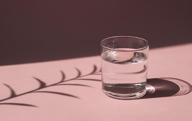 Szklanka wody oświetlona przez jasne słońce. przezroczyste naczynie z płynem na różowym stole. twarde cienie.