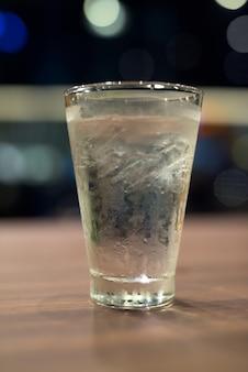 Szklanka wody pitnej na drewnianym stole w nocy