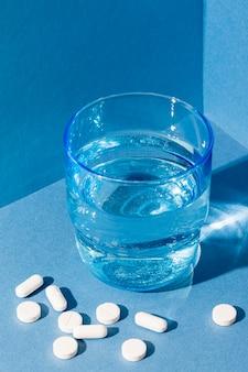 Szklanka wody pod wysokim kątem z pigułkami