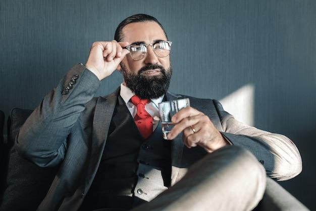 Szklanka wody. sukcesy biznesmen w okularach trzymając szklankę wody, siedząc w pokoju hotelowym