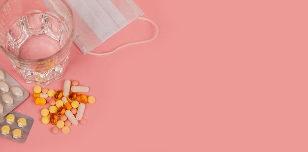 Szklanka wody, tabletki leku w blistrze i maska.