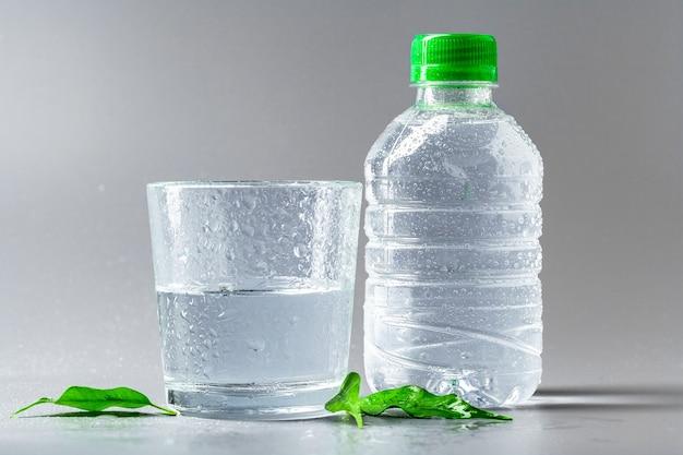 Szklanka wody z butelką na stole