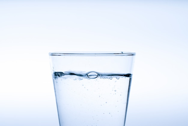 Szklanka wody z dolewaniem z butelki, studio strzał