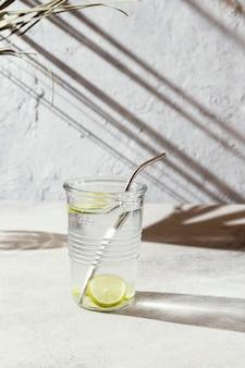 Szklanka wody z plasterkami cytryny na stole