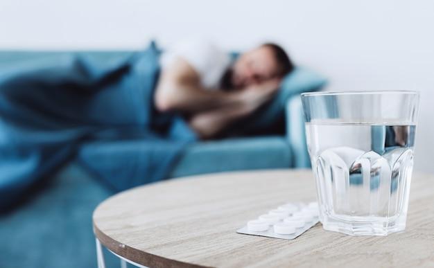 Szklanka wody z tabletkami na tle śpiącego chorego