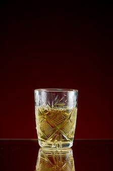 Szklanka z alkoholem w przezroczystej szklance z lodem i miętą na czerwonym