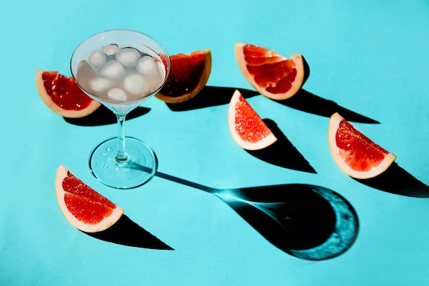 Szklanka z koktajlem i pokrojonymi grejpfrutami na niebieskiej powierzchni.