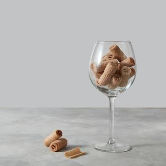 Szklanka z kremowym waflem toczy się po szarej marmurowej ścianie i kopiuje przestrzeń.