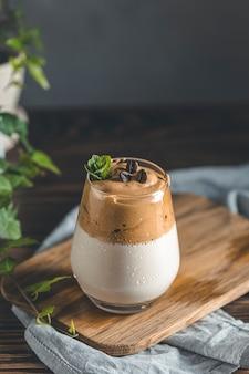 Szklanka z kroplami wody iced dalgona coffee, modnej puszystej kremowej bitej kawy
