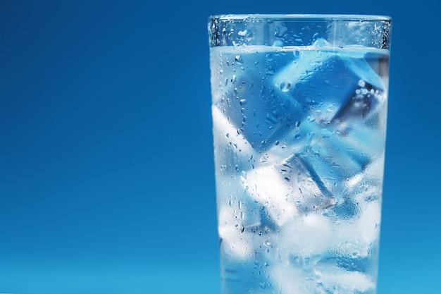 Szklanka z lodowatą wodą i kostkami lodu na niebieskiej powierzchni
