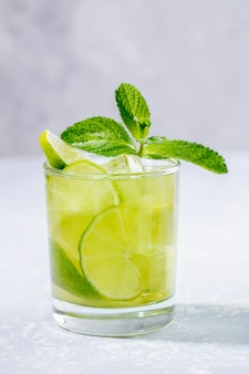 Szklanka z mrożoną zieloną herbatą matcha z limonką, lodem i miętą na szaro.