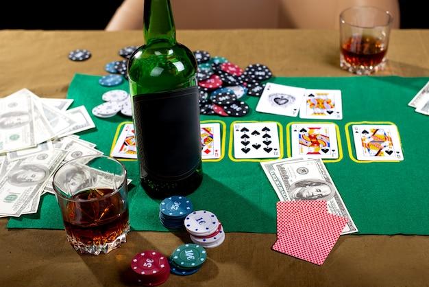 Szklanka z napojem alkoholowym i kartami w przestrzeni