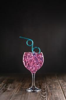 Szklanka z różowym koktajlem wypełnionym lodem na ciemnej powierzchni