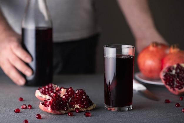 Szklanka z sokiem z granatów stoi na szarej betonowej powierzchni