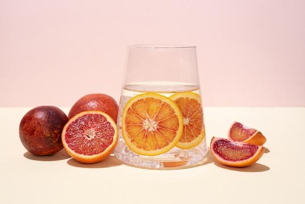 Szklanka z wodą funkcjonalną i plastrami owoców cytrusowych i czerwonych pomarańczy na żółto-różowym