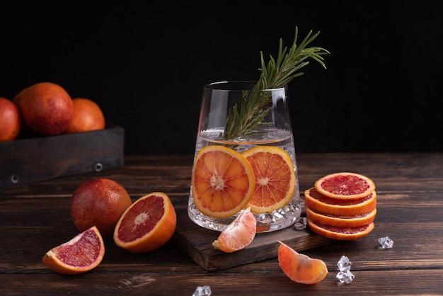 Szklanka z wodą funkcjonalną z plastrami czerwonych pomarańczy i rozmarynem