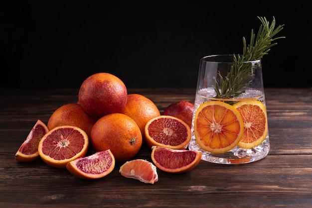 Szklanka z wodą i plasterkami czerwonej pomarańczy i owoców cytrusowych