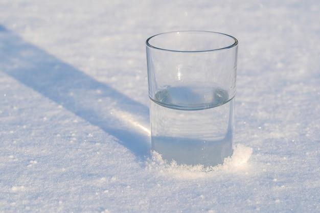 Szklanka z wodą na białym śniegu zimą, z bliska