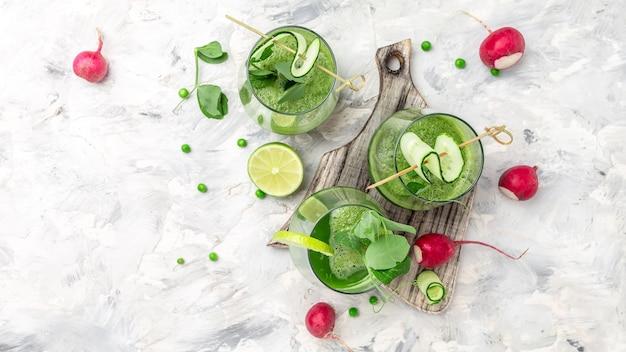 Szklanka z zielonymi domowymi koktajlami, koktajl detox, zielony świeży groszek, ogórek, rzodkiew, szpinak i limonka, baner, miejsce na przepis menu na tekst, widok z góry,