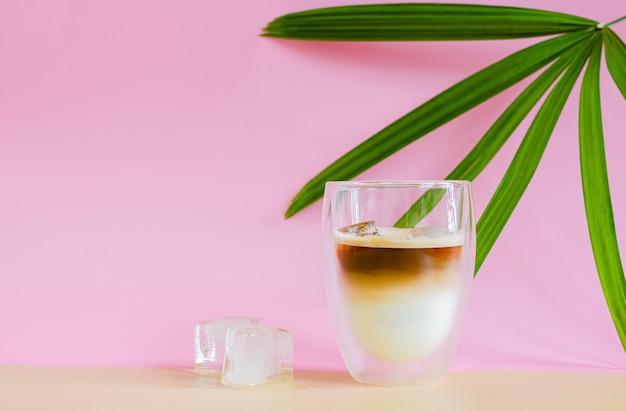 Szklanka zalewana parą kawy mieszającej mleko na brązowym i różowym tle z mrożoną kostką i liściem palmowym. koncepcja letniego drinka.