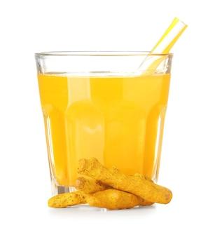 Szklanka zdrowego napoju z kurkumy na białym