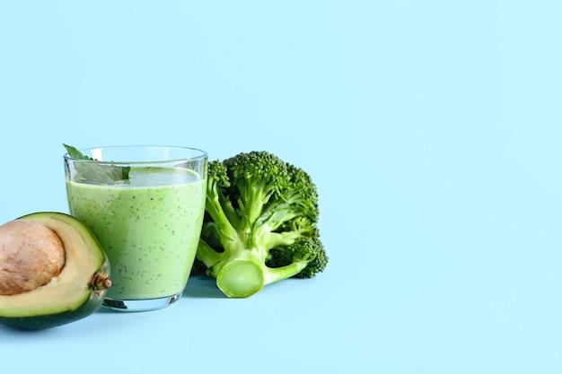 Szklanka zdrowego smoothie z awokado i brokułami na kolorowej powierzchni