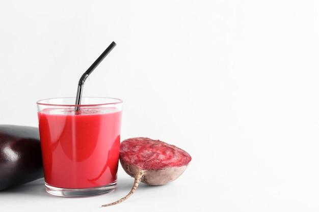 Szklanka zdrowego smoothie z burakiem i bakłażanem na białej powierzchni