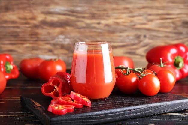 Szklanka zdrowego smoothie z pomidorami i papryką na powierzchni drewnianych