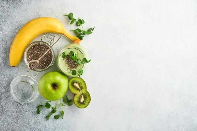 Szklanka zdrowego zielonego smoothie i składniki na smoothie, świeży szpinak, groszek microgreens, banan, kiwi, jabłko i nasiona chia na jasnoszarym tle betonu. zdrowe jedzenie napojów. widok z góry.