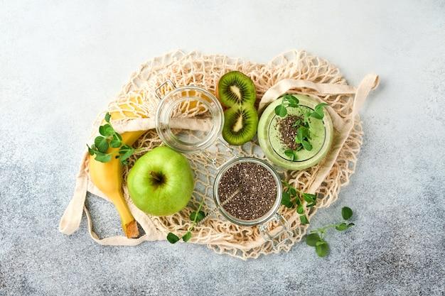 Szklanka zdrowego zielonego smoothie i składniki na smoothie, świeży szpinak, nasiona chia, groszek, banan, kiwi i jabłko w torbach wielokrotnego użytku na jasnoszarym betonowym tle. widok z góry.