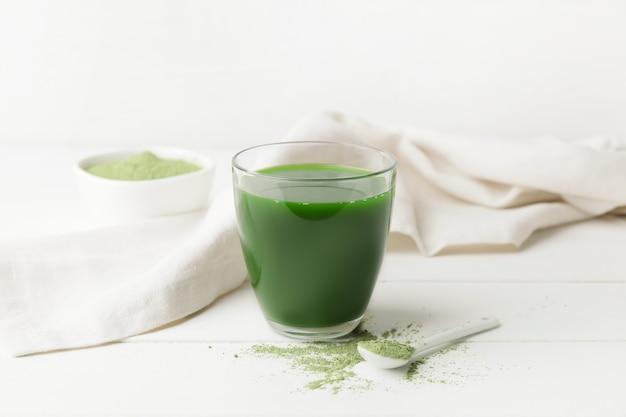 Szklanka ze świeżym sokiem z trawy pszenicznej i proszkiem na białym