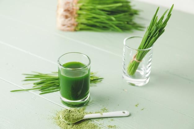 Szklanka ze świeżym sokiem z trawy pszenicznej i proszkiem na kolorowym drewnie