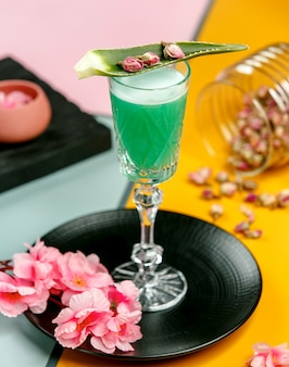 Szklanka zielonego koktajlu z dodatkiem aloesu i suszonych pąków róży