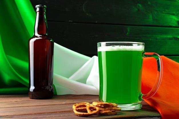 Szklanka zielonego piwa z banderą irlandii z bliska