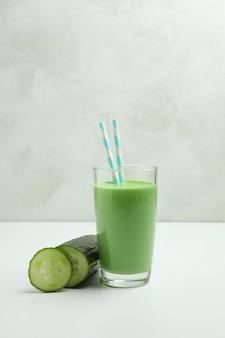 Szklanka zielonego smoothie i ogórka na białym stole