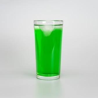 Szklanka zielonego soku z lodem na białym tle