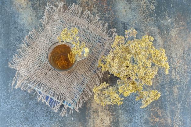 Szklanka zielonej herbaty i kwiaty na górze książki.