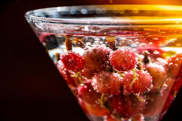 Szklanka zimnego orzeźwiającego letniego napoju z jagodami i kostkami lodu