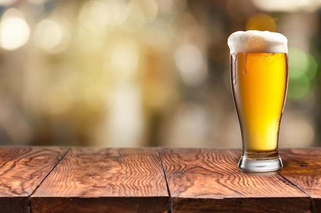 Szklanka zimnego orzeźwiającego piwa z pianką na drewnianym stole