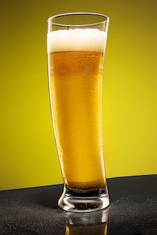 Szklanka zimnego pieniącego się piwa na starym drewnianym stole
