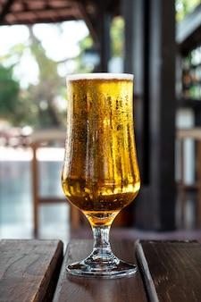 Szklanka zimnego piwa koloru bursztynowego z kondensacją na drewnianym stole w pubie. napój alkoholowy. koncepcja wypoczynku letniego.