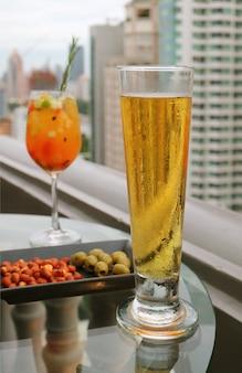 Szklanka zimnego piwa z beczki i świeżych owoców koktajl sangria na szklanym stole na tarasie baru na dachu