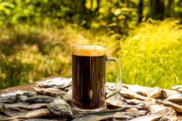 Szklanka zimnego, świeżego ciemnego piwa. piwo w ogrodzie i letni dzień