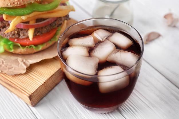 Szklanka zimnej coli ze smacznym burgerem na stole