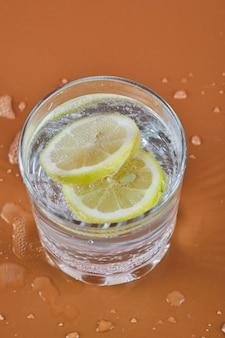 Szklanka zimnej orzeźwiającej lemoniady na pomarańczowej powierzchni