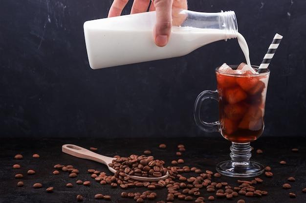 Szklanka zimnej parzonej kawy i nalane mleko z butelki