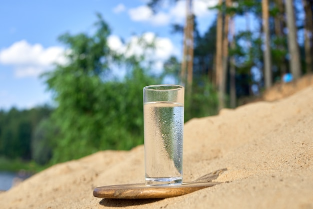 Szklanka zimnej wody na desce. piasek i drzewa na tle przyrody.