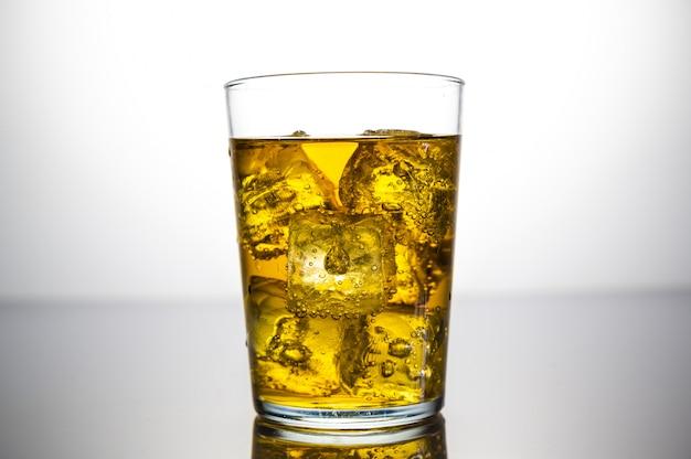 Szklanka żółtego napoju z kostkami lodu